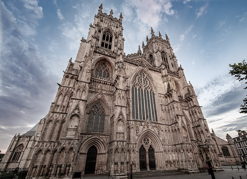 The York Minster in Deangate York. Medieval Gothic Cathedral with blue skies behind it. York Minster is full of dark history sites and haunted places in York England.