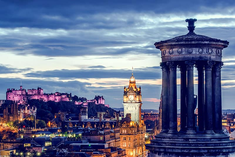 Best Ghost tours in Edinburgh - the Edinburgh skyline from Calton Hill - looking out at the castle and Balmoral hotel as dusk falls