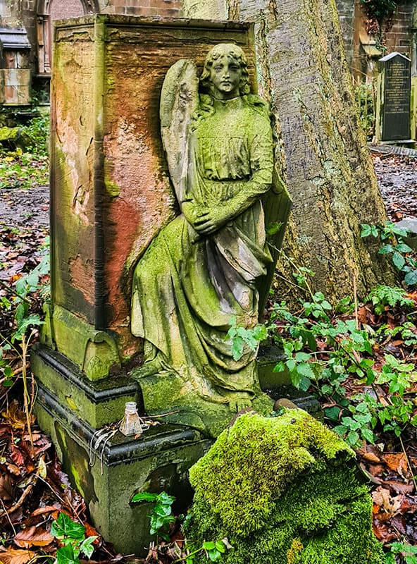 Moss covered tombstone with a monument of a winged angel
