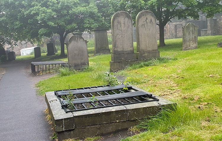Gravestones and mortsafes (caged cover over grave) in a graveyard.